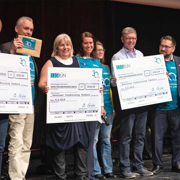 Acht GRÜN-MitarbeiterInnen nehmen auf einer Bühne drei Schecks über 3030 Euro entgegen