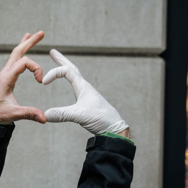 Eine Hand ohne Handschuh und eine Hand mit Handschuh formen gemeinsam ein Handherz