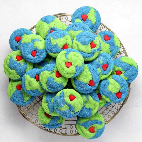 Kekse, die wie Weltkugeln aussehen mit roten Herzen darauf