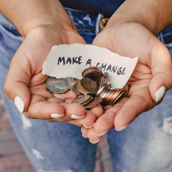 """Geöffnete Hände mit Kleingeld und einem Zettel, auf dem """"Make a Change"""" steht"""
