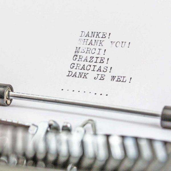 Blatt in Schreibmaschine mit dem Wort Dank in sechs Sprachen