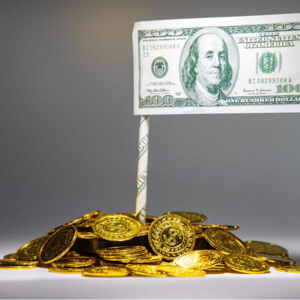 Ein Haufen Goldmünzen, in dem eine kleine Fahne mit einem 100-Dollar-Schein steckt