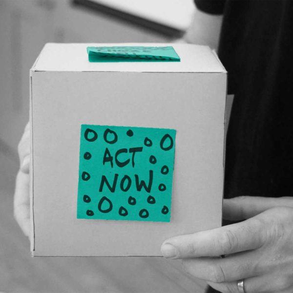 """Box mit grünem Zettel, auf dem """"Act now"""" steht"""