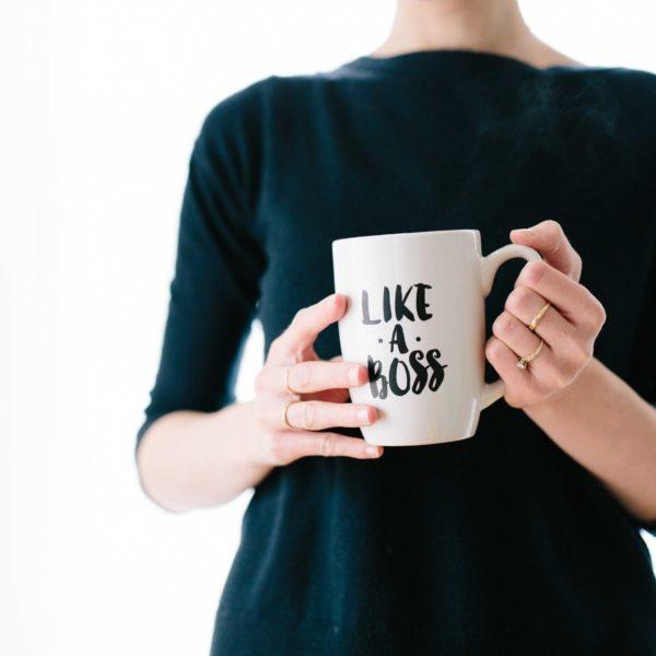 """Eine Frau hält eine weiße Kaffeetasse, auf der in schwarzer Schrift steht: """"Like a Boss."""""""