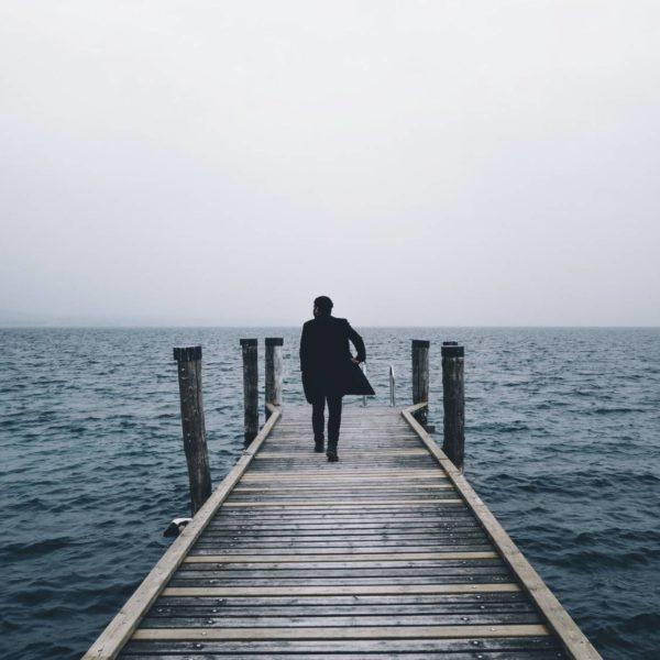 Mann mit dem Rücken zur Kamera auf einem Steg am nebligen Meer