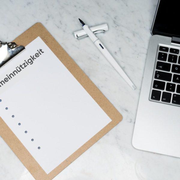 """Eine Liste mit der Überschrift """"Gemeinnützigkeit"""" neben einem offenen Füller und einem Laptop"""