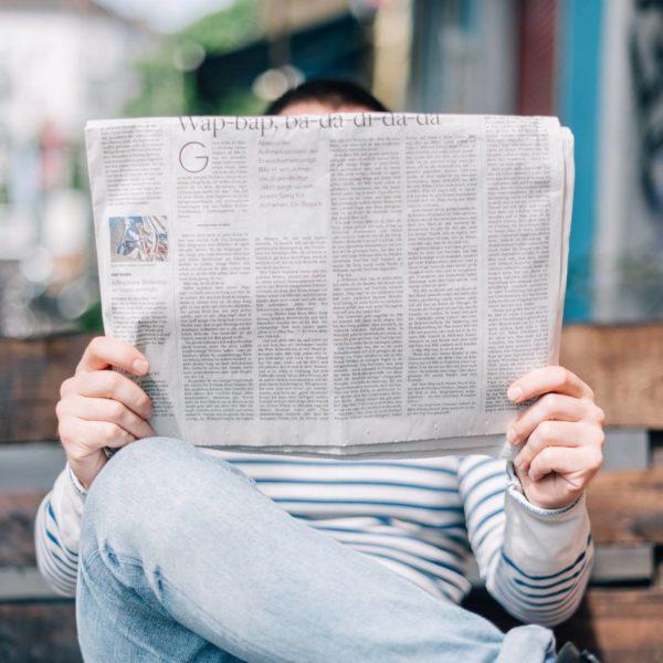 Mann sitzt auf Bank und liest Zeitung